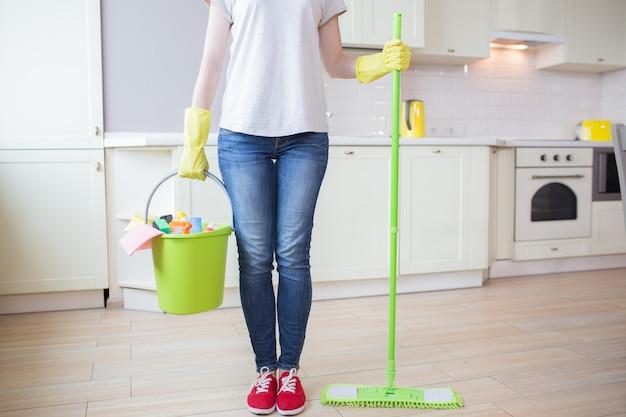 Cortar a vista da mulher fica na cozinha e detém vara com esfregão em uma mão e balde com equipamento de limpeza na outra. menina usa luvas amarelas.