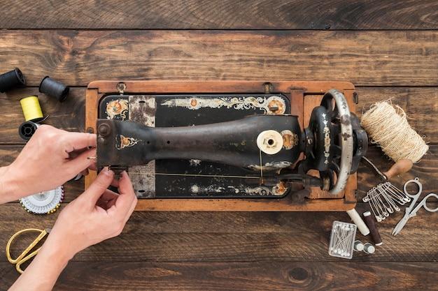 Cortar as mãos ajustando a linha na máquina de costura antiga