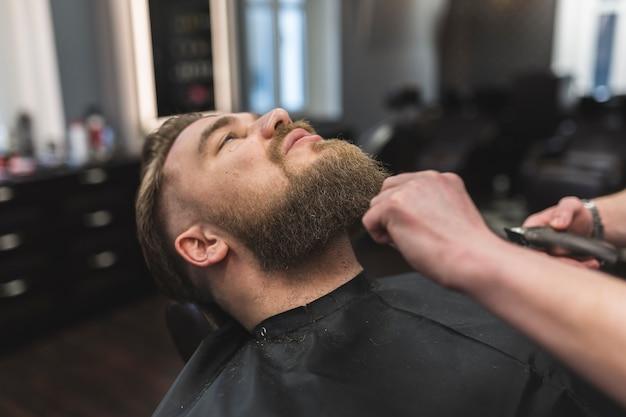 Cortar as mãos aparar barba do homem