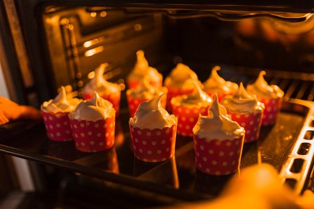 Cortar as mãos colocando cupcakes no forno