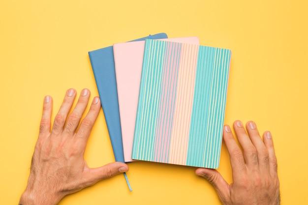 Cortar as mãos com cadernos com capas criativas