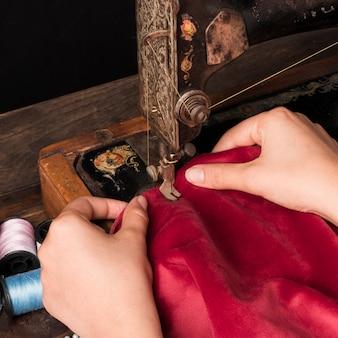 Cortar as mãos com tecido vermelho usando a máquina de costura