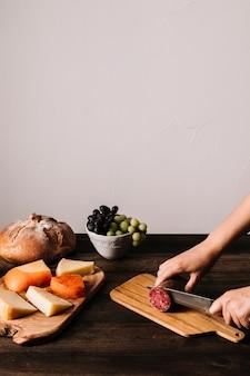 Cortar as mãos cortar salsicha com faca