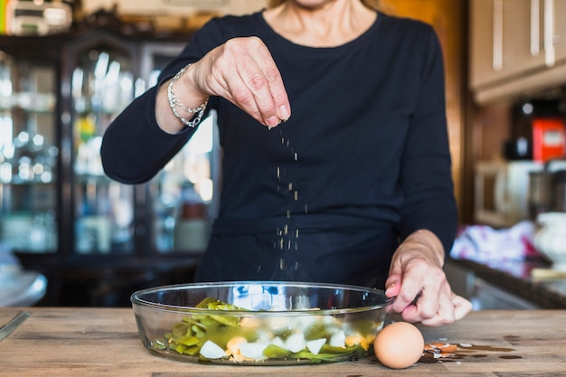 Cortar as mãos da mulher idosa, polvilhando o prato com sal