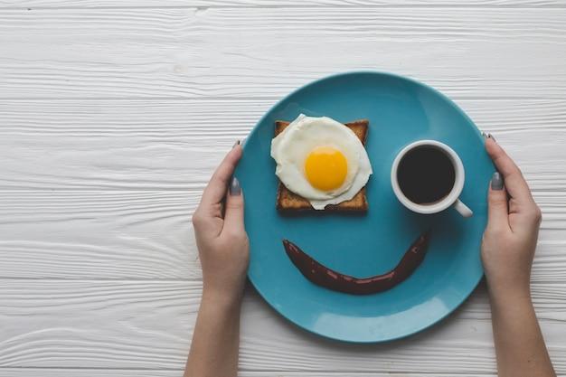Cortar as mãos segurando prato com café da manhã