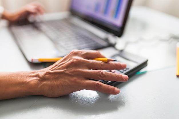 Cortar as mãos usando calculadora e laptop