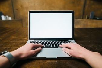 Cortar as mãos usando laptop moderno