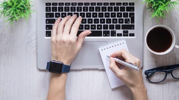Cortar as mãos usando o laptop e fazendo anotações