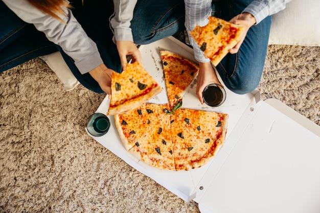 Cortar as meninas com pizza no chão