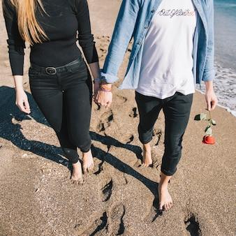 Cortar casal apaixonado caminhando na praia