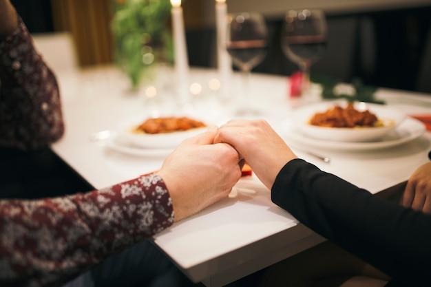 Cortar casal segurando as mãos na mesa