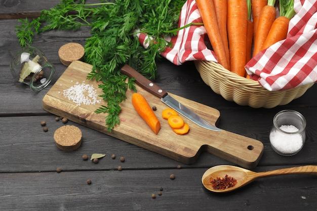 Cortar cenouras saudáveis na fatia na placa de desbastamento na cozinha