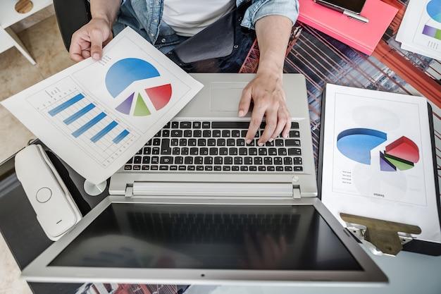 Cortar empregado usando laptop enquanto examina relatórios