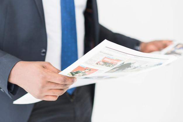 Cortar empresário de pé com jornal