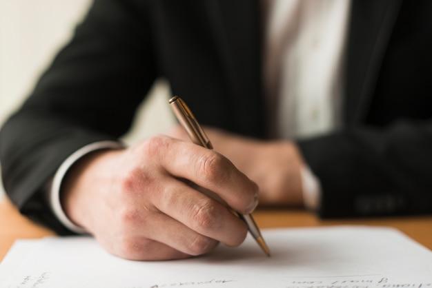 Cortar empresário escrevendo no papel