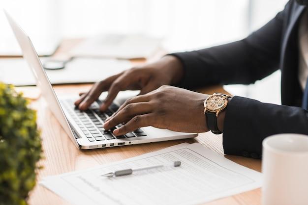 Cortar empresário étnico digitando no laptop