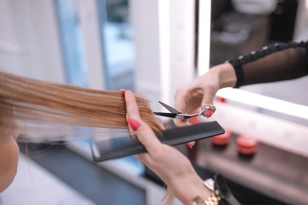Cortar estilista cortando cabelo termina no salão