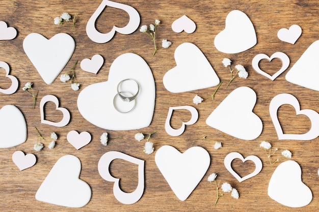 Cortar formas de coração branco com flores de respiração do bebê na mesa de madeira