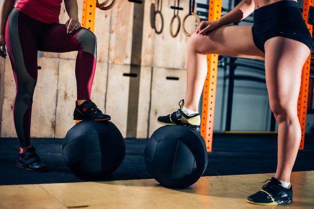Cortar foto de duas mulher colocar os pés nas bolas de medicina no ginásio
