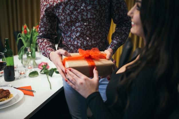 Cortar homem apresentando giftbox para mulher