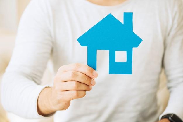 Cortar homem segurando casa de papel azul