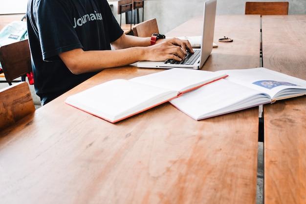 Cortar homem usando laptop perto de livros