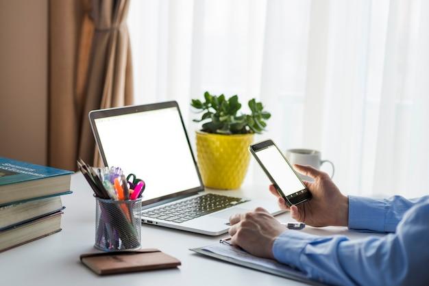 Cortar homem usando smartphone no escritório