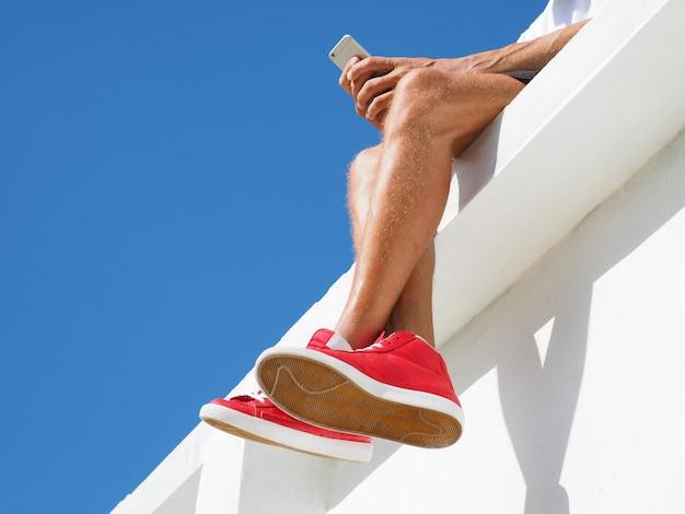 Cortar imagem. homem bronzeado em shorts e tênis vermelhos elegantes com um telefone celular. vista das pernas.