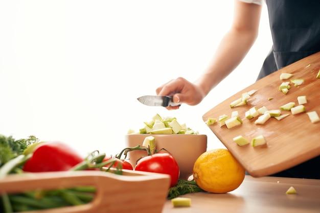 Cortar legumes em uma tábua de cortar ingredientes para salada de legumes frescos
