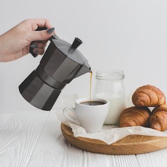 Cortar mão derramando café em copo