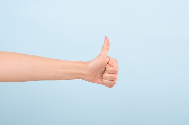 Cortar mão feminina com manicure brilhante segurando o polegar para aprovar contra a luz natural