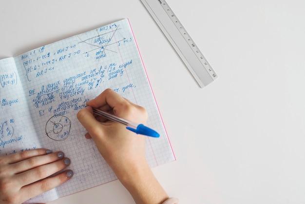 Cortar mãos femininas escrevendo no caderno