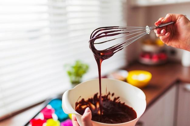 Cortar mãos misturando massa com batedor