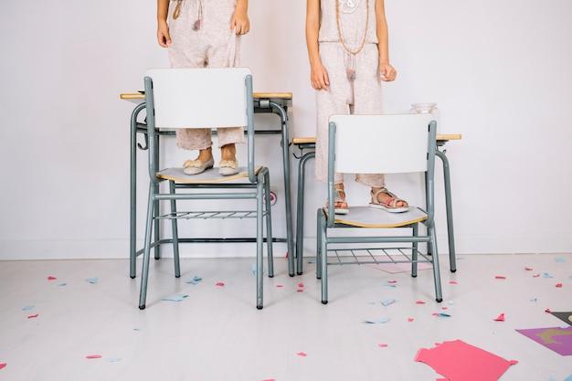 Cortar meninas de pé em cadeiras