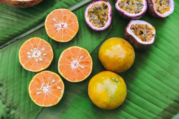 Cortar metade das laranjas frescas e maracujá em folhas de bananeira.