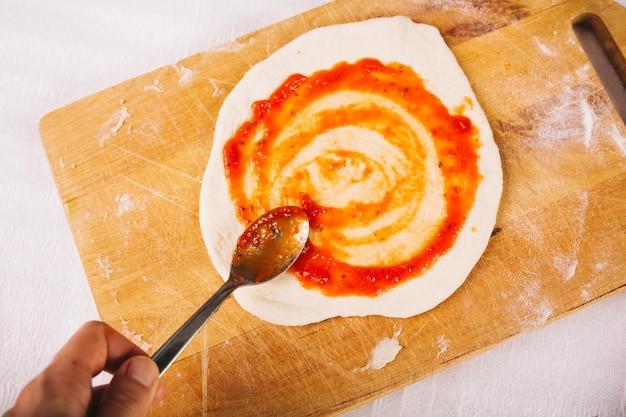 Cortar molho de mão na pizza