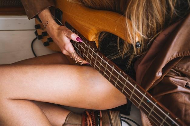 Cortar mulher com guitarra no chão Foto gratuita
