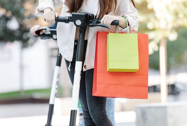 Cortar mulher na scooter com sacolas de compras na rua