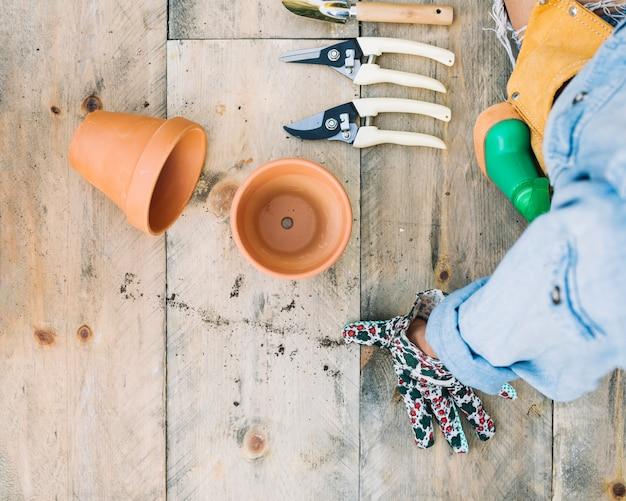 Cortar mulher perto de potes e ferramentas de jardinagem