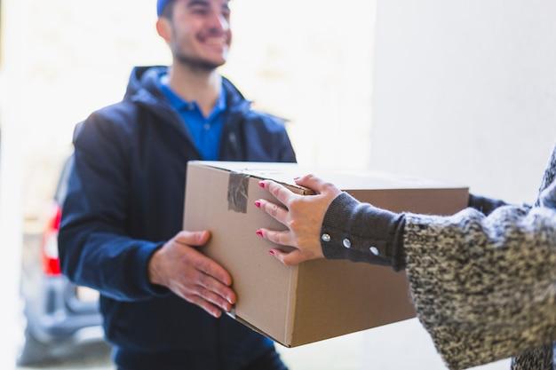 Cortar mulher recebendo caixa postal de mensageiro