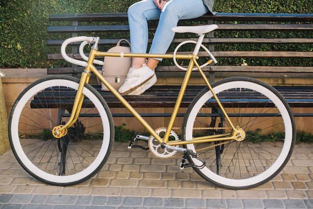 Cortar mulher sentada no banco atrás da bicicleta