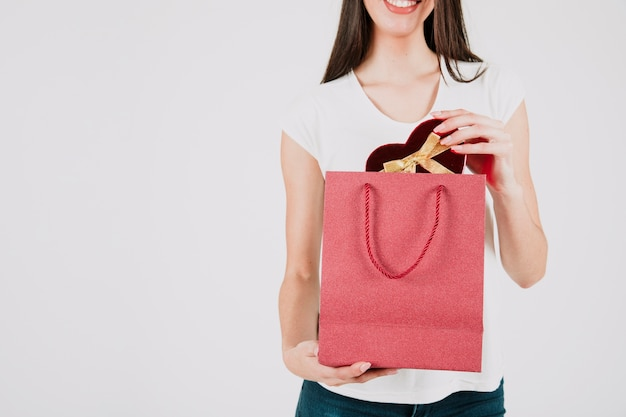 Cortar mulher sorridente com presente na bolsa de papel