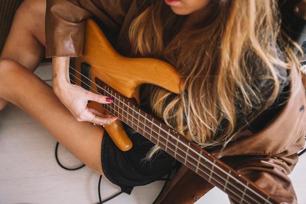 Cortar mulher tocando violão no chão