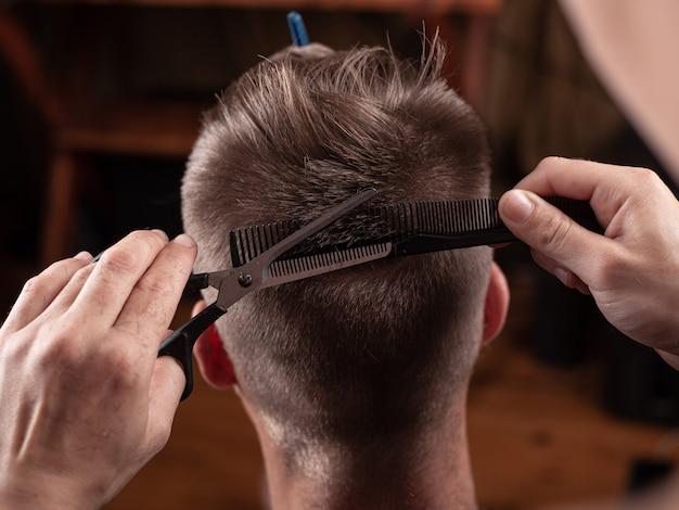Cortar o cabelo com uma tesoura no cabeleireiro, corte de cabelo bonito.