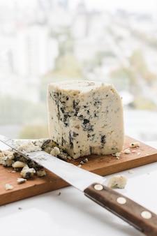 Cortar o queijo com uma faca na tábua de madeira sobre a mesa branca