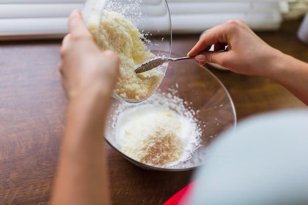 Cortar pessoa adicionando coco ralado a manteiga