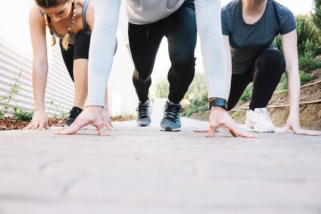 Cortar pessoas preparando-se para correr no pavimento