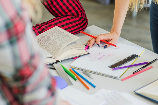 Cortar pessoas trabalhando na mesa com livros