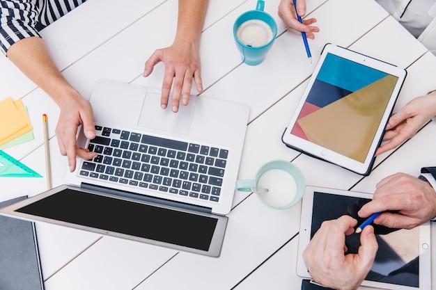 Cortar pessoas usando dispositivos na mesa de escritório