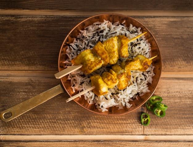 Cortar pimenta perto de arroz e kebab de frango